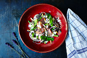 Octopus salad with green beans and onion. Red plate standing on the middle of the frame. Surface is a dark blue metal surface with a cloth on side.