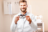 Ophthalmologist holding try-on tool for lenses selection in front of the eye chart in the cabinet. Image with fucus on the hands and glasses