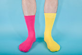 """Man standing against a blue background wearing bright coloured odd socks.Concepts, clashing, difference, wrong, etc"""