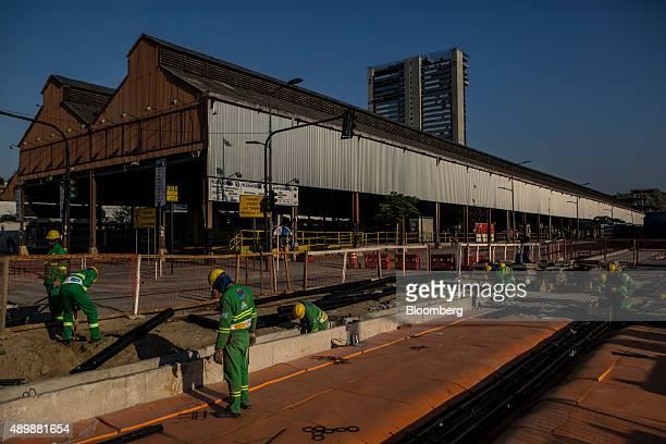 Odebrecht SA contractors build a railway next to a bus terminal in Rio de Janeiro Brazil on Thursday Sept 24 2015 Rio de Janeiro is undergoing a...