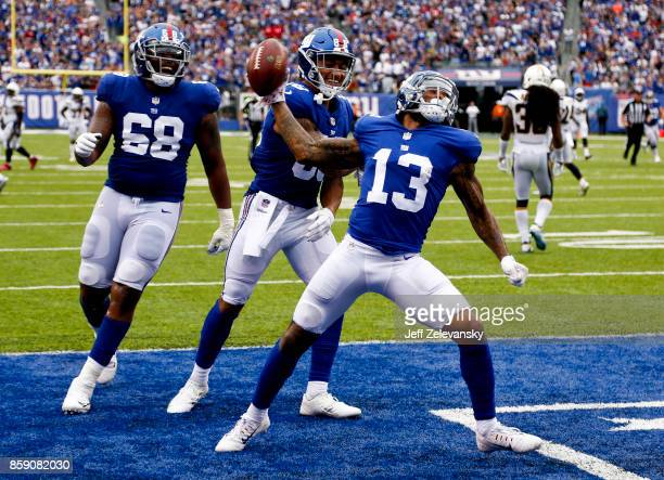 Odell Beckham of the New York Giants celebrates a touchdown with teammates Evan Engram and Bobby Hart during their game at MetLife Stadium against...