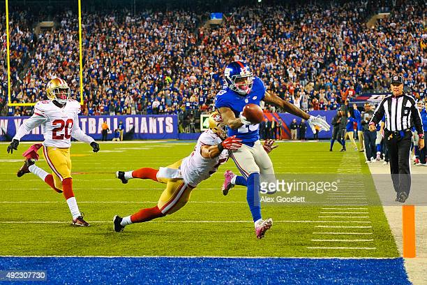 Odell Beckham of the New York Giants scores a touchdown while Michael Wilhoite of the San Francisco 49ers attempts to tackle him in the third quarter...