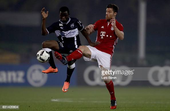 Odeni George of Eupen is challenged by Xavi Alonso of Muenchen during the friendly match between Bayern Muenchen and KAS Eupen on January 10 2017 in...