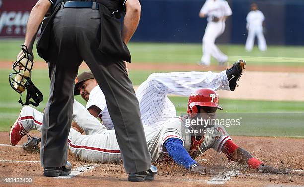 Odubel Herrera of the Philadelphia Phillies dives as he scores on a wild pitch ahead of the tag of Tyson Ross of the San Diego Padres during the...