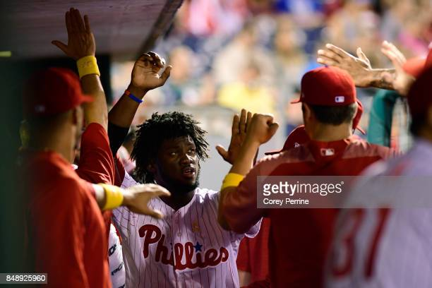 Odubel Herrera of the Philadelphia Phillies highfives teammates after being driven in by teammate JP Crawford against the Oakland Athletics during...