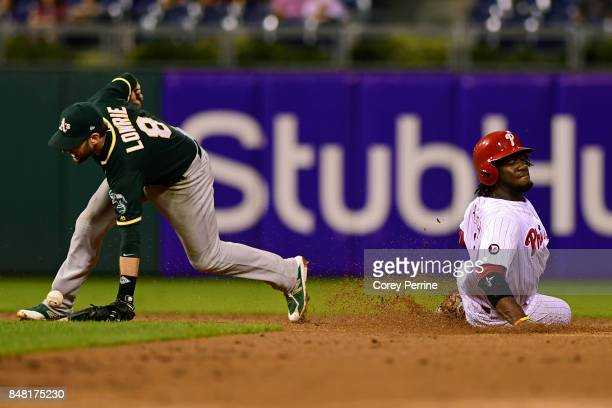 Odubel Herrera of the Philadelphia Phillies is safe at second base as Jed Lowrie of the Oakland Athletics can't handle the ball during the fourth...
