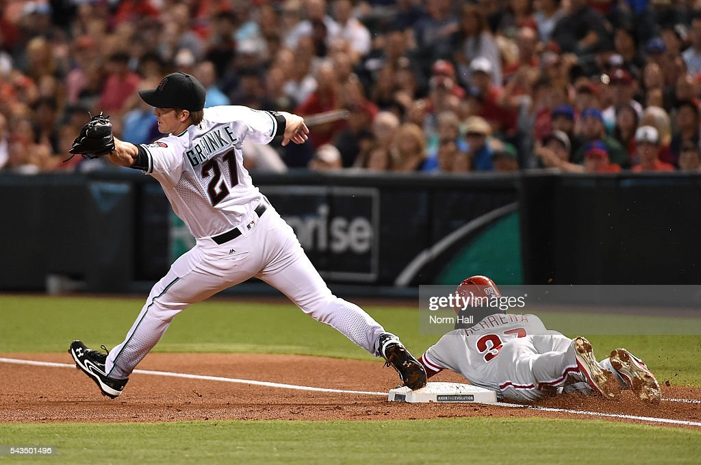 Odubel Herrera #37 of the Philadelphia Phillies safely slides into first base as Zack Greinke #21 of the Arizona Diamondbacks stretches to make a play on a wide throw during the first inning at Chase Field on June 28, 2016 in Phoenix, Arizona.