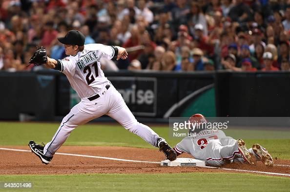 Odubel Herrera of the Philadelphia Phillies safely slides into first base as Zack Greinke of the Arizona Diamondbacks stretches to make a play on a...