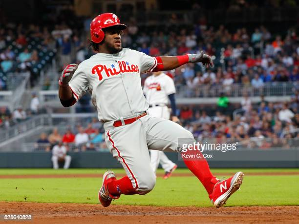 Odubel Herrera of the Philadelphia Phillies slides safely into third base after hitting a triple and then scores on a throwing error by Ozzie Albies...