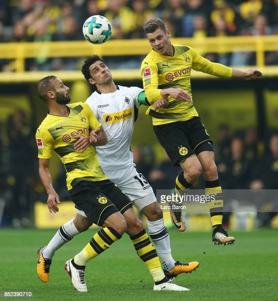 Oemer Toprak of Dortmund Lars Stindl of Moenchengladbach and Lukasz Piszczek of Dortmund fight for the ball during the Bundesliga match between...