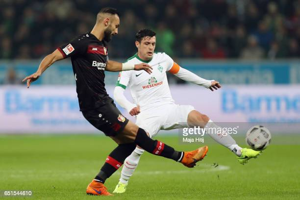 Oemer Toprak of Leverkusen is challenged by Zlatko Junuzovic of Bremen during the Bundesliga match between Bayer 04 Leverkusen and Werder Bremen at...