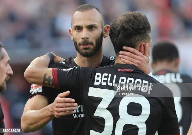 Oemer Toprak of Leverkusen shakes hands with Karim Bellarabi during the Bundesliga match between Bayer 04 Leverkusen and VfL Wolfsburg at BayArena on...