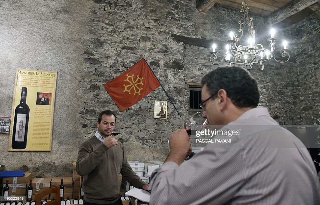 Oenologist Matthieu Dubernet (L) and Frantz Venes (R), owner of Chateau Massamier La Mignarde winery, taste a blend of grapes from the 'Domus-Maximus' Chateau Massamier La Mignarde wineyard in the cellar of the domain in Pepieux, southern France, on May 21 2014.