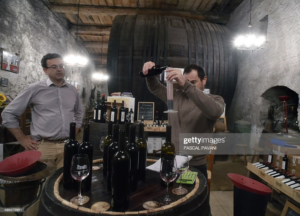 Oenologist Matthieu Dubernet (R) and Frantz Venes (L), owner of Chateau Massamier La Mignarde winery, taste a blend of grapes from the 'Domus-Maximus' Chateau Massamier La Mignarde wineyard in the cellar of the domain in Pepieux, southern France, on May 21 2014. AFP PHOTO / PASCAL PAVANI