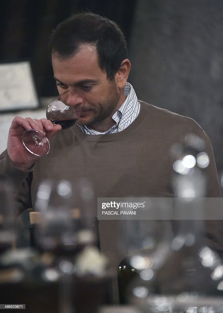 Oenologist Matthieu Dubernet tastes a blend of grapes from the ' Domus-Maximus' Chateau Massamier La Mignarde wineyard in the cellar of the domain in Pepieux southwestern France, on May 21, 2014 .