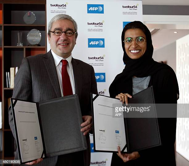 CEO of Agence France Presse Emmanuel Hoog poses for a picture with Noura AlKaabi twofour54 Chief Executive Officer on November 17 after signing an...