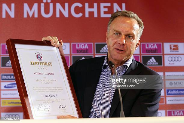 CEO of Bayern Muenchen KarlHeinz Rummenigge shows the certificate of the chronicle of FC Bayern Muenchen during its presentation on November 10 2010...