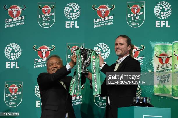 CEO of Carabao Group Sathien Setthasit and former French international footballer Emmanuel Petit raise the EFL Carabao Cup after the first draw for...