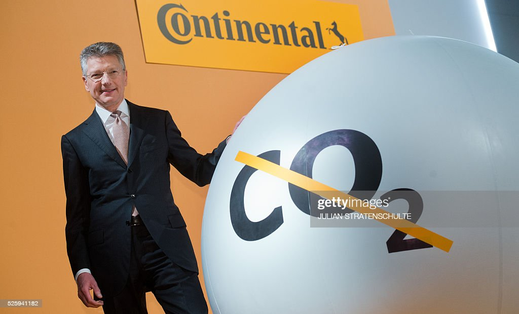 CEO of German car parts specialist Continental Elmar Degenhart poses next to ball with the crossed out lettering 'CO2' during the company's annual general meeting on April 29, 2016 in Hanover, northern Germany. Continental said it got off to a good start to the year, driven largely by strong demand for its tyres. / AFP / dpa / Julian Stratenschulte / Germany OUT