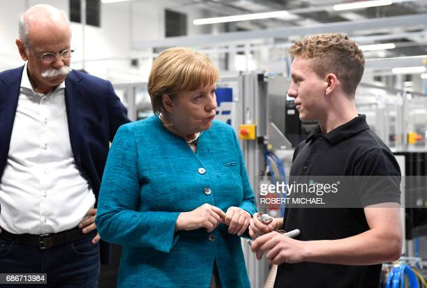 CEO of German carmaker Daimler and MercedesBenz Dieter Zetsche looks as German Chancellor Angela Merkel talks to a worker during a visit to the new...