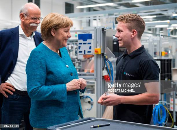 CEO of German carmaker Daimler and MercedesBenz Dieter Zetsche looks as German Chancellor Angela Merkel talks to a trainee during a visit to the new...