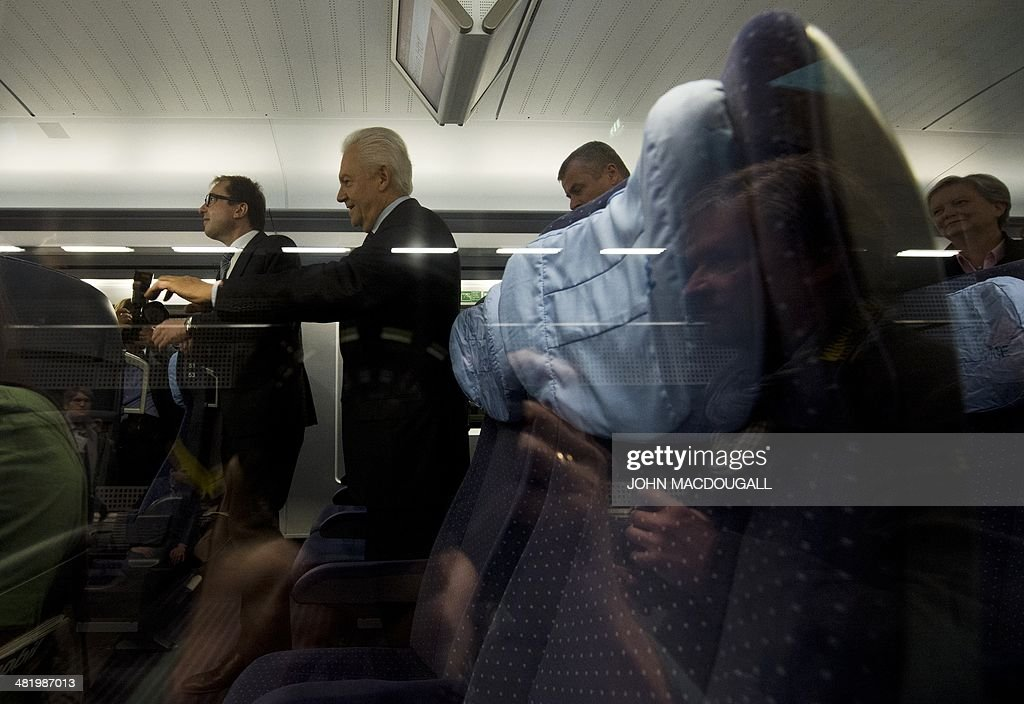 CEO of German railway giant Deutsche Bahn (DB) Ruediger Grube (2nd from L) and German Transport Minister Alexander Dobrindt (L) walks through a carriage of a Siemens InterCity Express (ICE) 3 during a presentation of the last of 8 new ICE 3 trains recently delivered to DB, at Berlin's main railway station April 2, 2014.