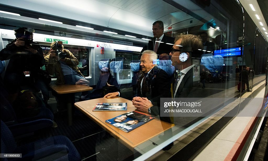 CEO of German railway giant Deutsche Bahn (DB) Ruediger Grube (C) and German Transport Minister Alexander Dobrindt (R) sit in a carriage of a Siemens InterCity Express (ICE) 3 train during a presentation of the last of 8 new ICE 3 trains recently delivered to DB, at Berlin's main railway station April 2, 2014. AFP PHOTO / JOHN MACDOUGALL
