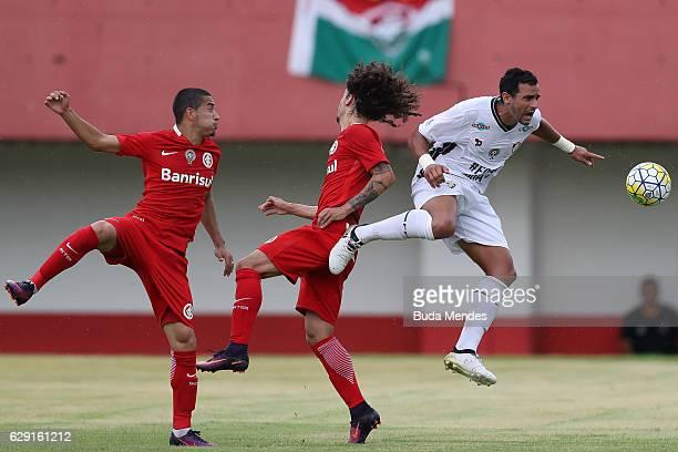 of Henrique Dourado Fluminense struggles for the ball with Valdvia and William of Internacional during a match between Fluminense and Internacional...