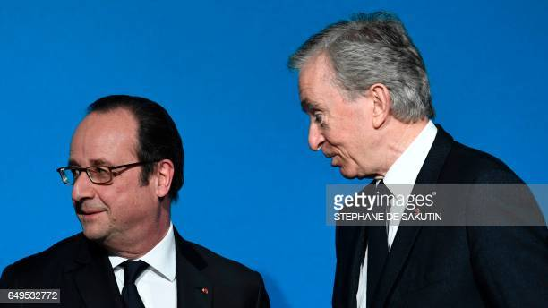 CEO of LVMH Bernard Arnault looks at French president Francois Holland during a press conference to unveil a new museum in Paris on March 8 2017 The...