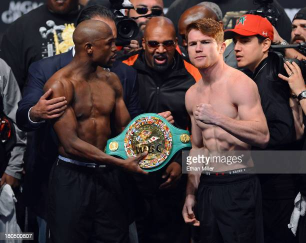 CEO of Mayweather Promotions Leonard Ellerbe looks on as boxer Floyd Mayweather Jr tries to get boxer Canelo Alvarez to hold a WBC belt as they pose...