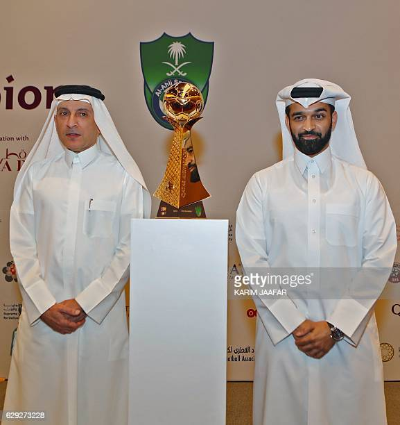 CEO of Qatar Airways Akbar alBaker and Secretary General of the Qatar 2022 Supreme Committee Hassan alThawadi pose with the cup of the match during a...