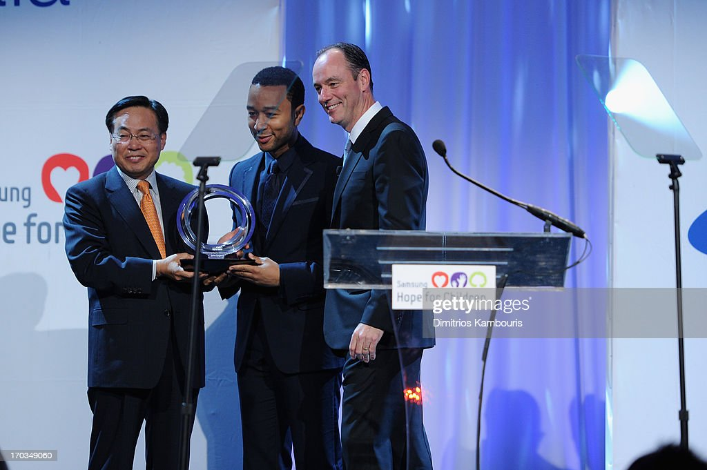CEO of Samsung Electronics America Y.K. Kim, John Legend and President of Samsung Electronics America Tim Baxter speak onstage at the Samsung's Annual Hope for Children Gala at Cipriani's in Wall Street on June 11, 2013 in New York City.