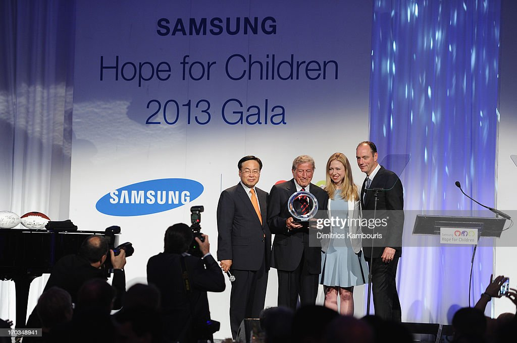 CEO of Samsung Electronics America Y.K. Kim, Tony Bennett, Chelsea Clinton and President of Samsung Electronics America Tim Baxter speak onstage at the Samsung's Annual Hope for Children Gala at Cipriani's in Wall Street on June 11, 2013 in New York City.