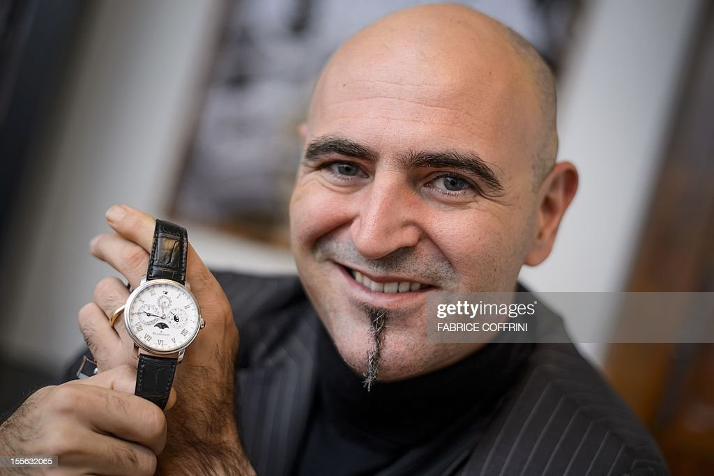 CEO of Swiss watchmakers Blancpain Marc Hayek poses with a Chinese themed limited edition model of a watch by Swiss watchmaker Blancpain which shows...