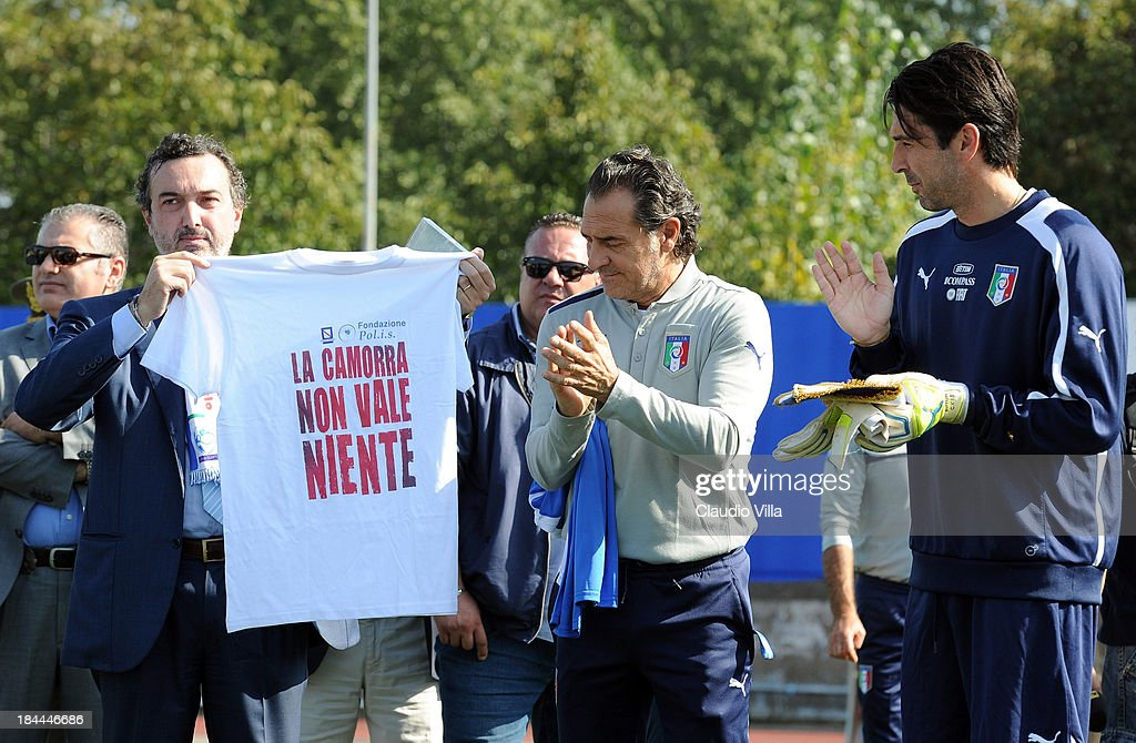 PM of the DDA in Naples Antonello Ardituro holds a t-shirt that reads 'The Camora is worth nothing' as Coach Cesare Prandelli and goalkeeper Gianluigi Buffon of Italy look on ahead of a training session on October 14, 2013 in Naples, Italy. The training session was organised at Quarto, a football pitch built on land confiscated from the Camorra - the Neapolitan Mafia, as part of the fight against the mafia.