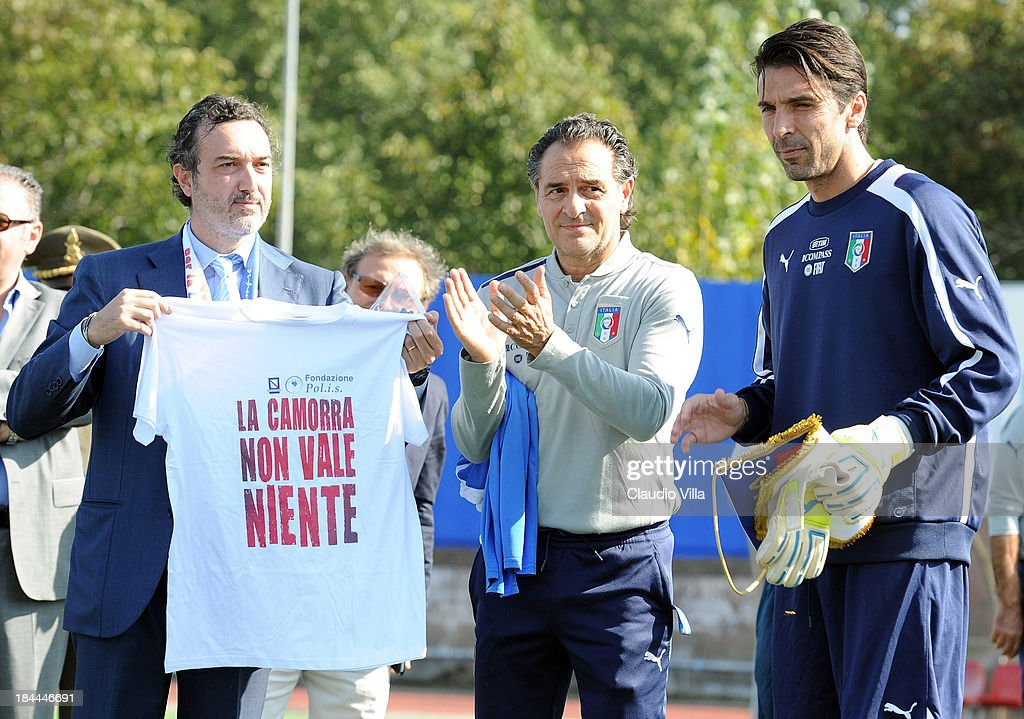 PM of the DDA in Naples Antonello Ardituro holds a t-shirt that reads 'The Camora is worth nothing' as Coach <a gi-track='captionPersonalityLinkClicked' href=/galleries/search?phrase=Cesare+Prandelli&family=editorial&specificpeople=742442 ng-click='$event.stopPropagation()'>Cesare Prandelli</a> and goalkeeper Gianluigi Buffon of Italy look on ahead of a training session on October 14, 2013 in Naples, Italy. The training session was organised at Quarto, a football pitch built on land confiscated from the Camorra - the Neapolitan Mafia, as part of the fight against the mafia.