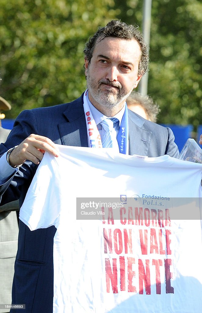 PM of the DDA in Naples Antonello Ardituro holds a t-shirt that reads 'The Camora is worth nothing' ahead of a Italy training session on October 14, 2013 in Naples, Italy. The training session was organised at Quarto, a football pitch built on land confiscated from the Camorra - the Neapolitan Mafia, as part of the fight against the mafia.