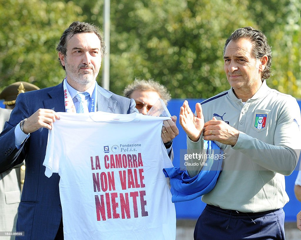 PM of the DDA in Naples Antonello Ardituro holds a t-shirt that reads 'The Camora is worth nothing' as Coach Cesare Prandelli of Italy looks on ahead of a training session on October 14, 2013 in Naples, Italy. The training session was organised at Quarto, a football pitch built on land confiscated from the Camorra - the Neapolitan Mafia, as part of the fight against the mafia.