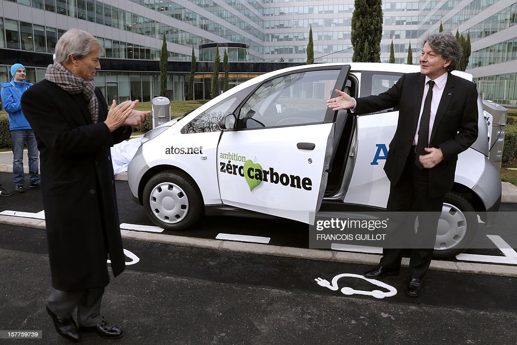 CEO of the IT services company Atos, Thierry Breton (R) and French industrial group Bollore's head Vincent Bollore pose next to a 'MyCar' electric car, on December 6, 2012 in Bezons, north of Paris, after announcing during a joint press conference the launching of My Car, the first Atos electric car fleet powered by solar panels. AFP PHOTO FRANCOIS GUILLOT