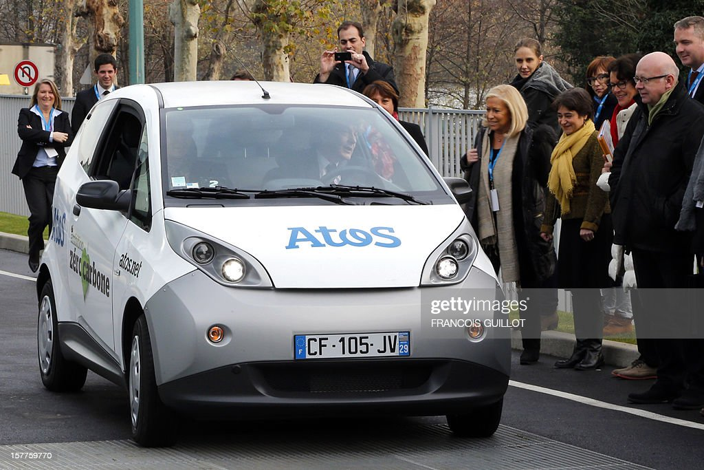 CEO of the IT services company Atos, Thierry Breton (C) drives a 'MyCar' electric car beside French industrial group Bollore's head Vincent Bollore (L), on December 6, 2012 in Bezons, north of Paris, after announcing during a joint press conference the launching of My Car, the first Atos electric car fleet powered by solar panels.