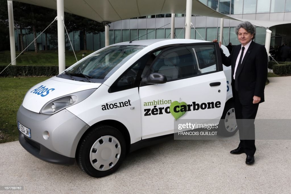 CEO of the IT services company Atos, Thierry Breton poses next to a 'MyCar' electric car, on December 6, 2012 in Bezons, north of Paris, after announcing the launching of My Car, the first Atos electric car fleet powered by solar panels, during a joint press conference with French industrial group Bollore's head. AFP PHOTO FRANCOIS GUILLOT