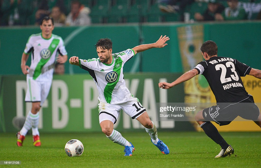 of Wolfsburg is challenged by Andreas Hofmann of Aalen during the second round DFB cup match between VfL Wolfsburg and Vfr Aalen at Volkswagen Arena on September 24, 2013 in Wolfsburg, Germany.