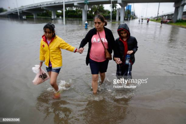 Ofelia Castro leads her grandchildren across a flooded street as they continue an hours long trek from their flooded house in the Edgewood area of...