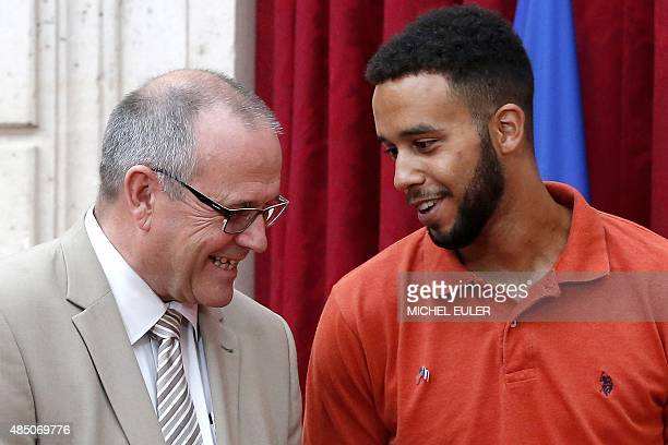 Offduty serviceman Anthony Sadler talks with British business consultant Chris Norman on August 24 2015 during a reception at the Elysee Palace in...