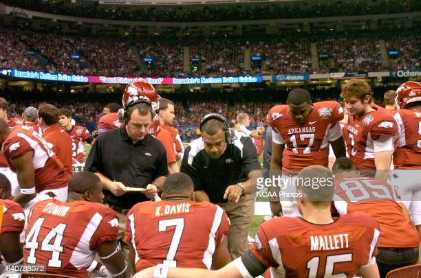 Offensive coordinator Garrick McGee of the University of Arkansas talks with his players as running backs coach Tim Horton looks on during the first...