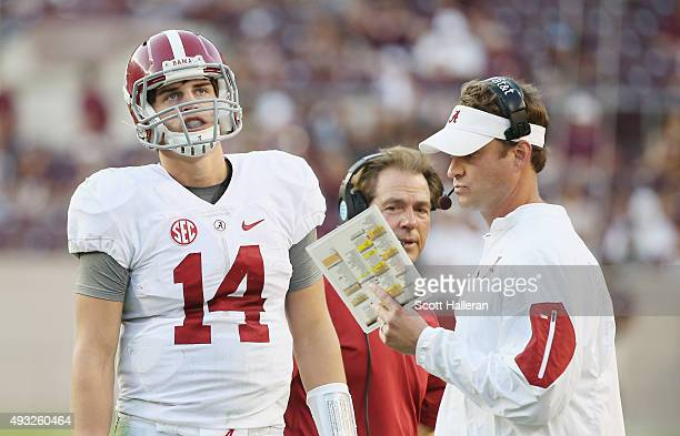 Offensive coordinator Lane Kiffin of the Alabama Crimson Tide chats with his quarterback Jake Coker on the sideline as head coach Nick Saban looks on...