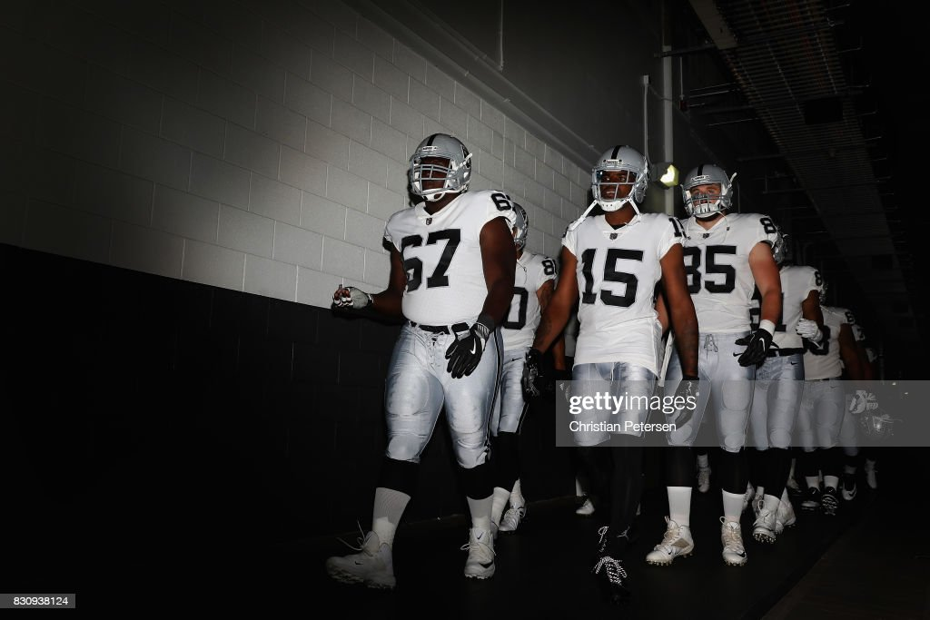 Offensive guard Oni Omoile #67, wide receiver Michael Crabtree #15 and tight end Ryan O'Malley #85 of the Oakland Raiders lead teamamtes onto the field before the NFL game against the Arizona Cardinals at the University of Phoenix Stadium on August 12, 2017 in Glendale, Arizona. The Cardinals defeated the Raiders 20-10.