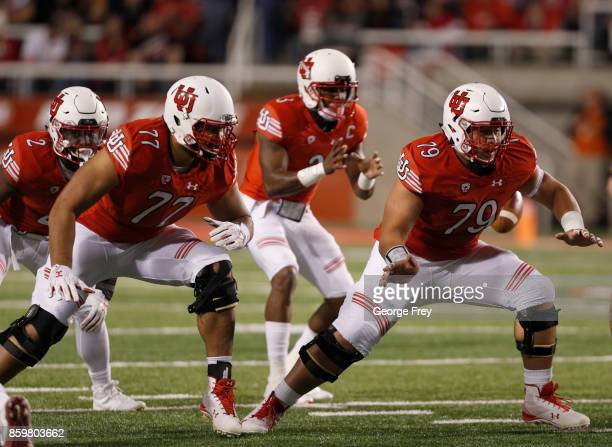 Offensive lineman Darrin Paulo of the Utah Utes and offensive lineman Jordan Agasiva of the Utah Utes look to block during the first half of an...