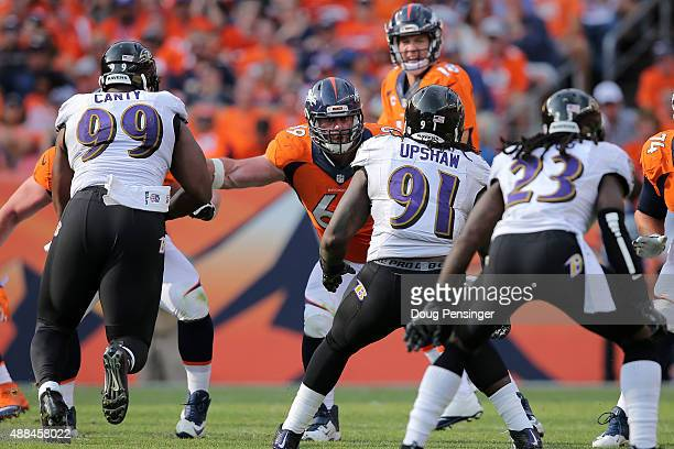 Offensive lineman Evan Mathis of the Denver Broncos defends the line of scrimmage against Chris Canty and Courtney Upshaw of the Baltimore Ravens at...