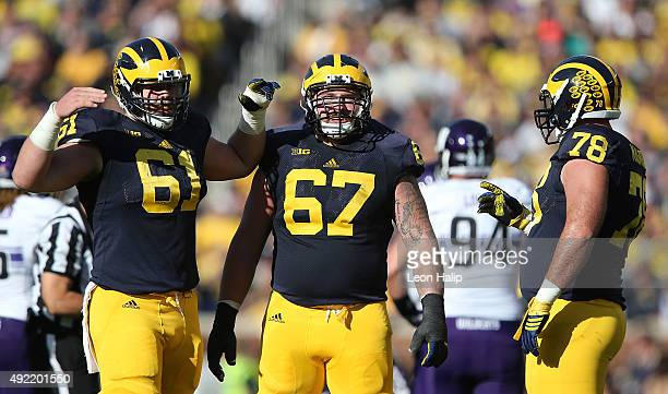 Offensive lineman Graham Glasgow Kyle Kalis and Erik Magnuson of the Michigan Wolverines look to the sidelines during the second quarter of the game...